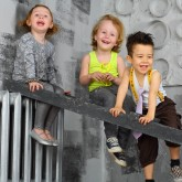 Three happy children sitting on the stairs near the gray wall